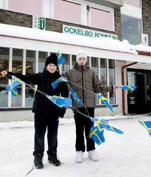 Ockelboborna Magnus Norén och Simon Sundberg med svenska flaggor utanför kommunhuset på torget i Ockelbo i samband med att Daniel Westling och kronprinsessan Victoria på tisdagen tillkännagivit sin förlovning