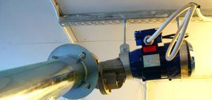 Med hjälp av en elmotor transporteras bränslet från förrådet till pannan.