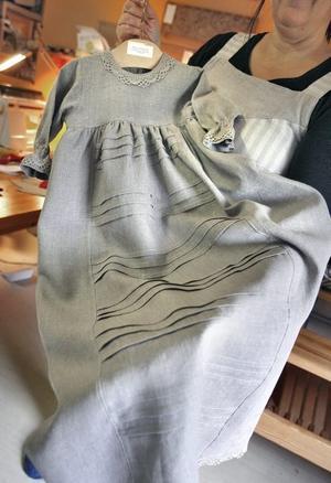 En dopklänning i linne som ska säljas i en barnklädesaffär i Stockholm.