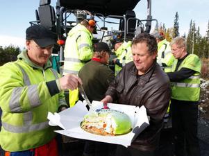 Roland Gullberg från Strömsnäs, tar sig en rejäl bit av tårtan som Johnny Hallquist bjuder vägarbetarna på.