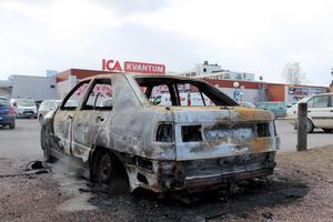 På parkeringen står en bil som brändes ned natten mot i onsdags.