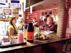 Nöden är uppfinningarnas moder. Eftersom kommunen inte velat erbjuda någon lokal till Woodpeckers har de gjort det bästa av situationen och skapat en gemytlig atmosfär i industrilokalen på Sörby Urfjäll. Lisa Fahlström, medlem sedan 1970-talet och före detta ordförande, står bakom disken och serverar medlemmarna. Den här onsdagen dricks det mest kaffe och läsk.