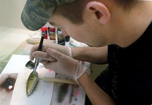 Med airbrush målar Benny Backeby mönstren på de wobblers och jerkbaits han tillverkar.