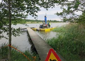 Vägarbete i Hässlösundet. Den nya bron till Björnön kommer att gå söder om dagens bro. På flotten jobbar Dykeriets Urban Lord och Erik Törnell.
