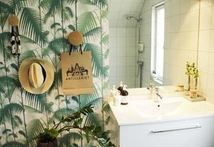Grönt och turkost är återkommande accentfärger hemma hos Josefine, som här i badrummet med en palmtapet från Cole & Son.