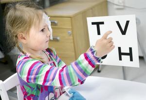 Hanna Larsson pekar på bokstäverna för att visa att hon ser vilka bokstäver som finns på tavlan som används när synen undersöks.
