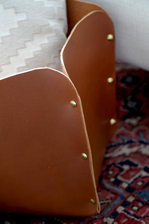 Läderkorgen som så småningom ska husera leksaker är gjord i ett stort stycke läder. Monica Karlstein bestämde storleken på bottenplattan samt höjden på kanterna och ritade sedan upp ett korsformat mönster med blyerts på lädret och klippte ut. Hålen för skruvnitarna gjordes med skruvdragare. Man kan också göra hål med syl och sy ihop kanterna i stället.