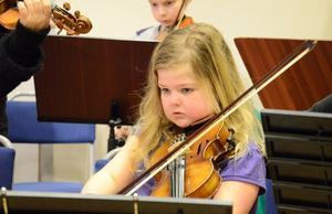 Violonisten Angelica Lönnström Karlsson är koncentrerad på sin insats i konserten på Kyrkbacksskolan i Kopparberg. I bakgrunden syns Oscar Harju.