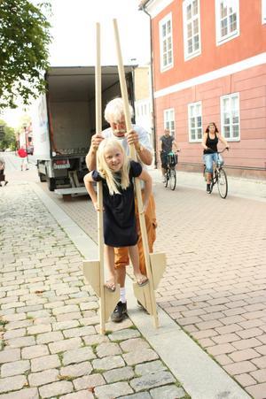Norah Anderson går på styltor med hjälp av Olov Mejman.