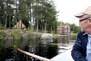 Lars Karlström, ordförande i Bredsjöns/Slättmons byalag konstaterar att det är flera i byn som ställt upp ideellt för att förverkliga möjligheterna till naturturism. I bakgrunden en av kåtorna och den halvfärdiga bastun på en udde i Bredsjön.