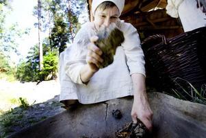 """KROSSAR RABARBER. Ann-Christin Elfström krossar rabarberrötter med en sten. De ska sedan användas till att växtfärga garner – som förhoppningsvis ska bli röda. """"Jag har ingen aning om hur det blir"""", säger hon med ett leende."""