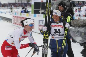 Charlotte Kalla gratulerar tisdagens överlägsna vinnare Marit Björgen efter hennes målgång.