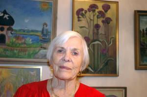 Leah Pettersson ser inte ut att vara 90 år. Men det fyller hon faktiskt den 5 januari. Bakom henne en del av hennes många målningar från åren som gått.