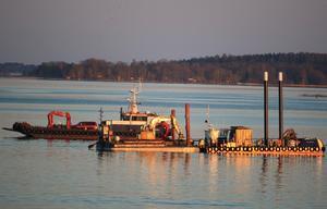 Med kvällssol får denna marina utrustning på väg att ta upp båtvraket i hamnen vid det gamla kraftverket en glans som gör den riktigt ståtlig