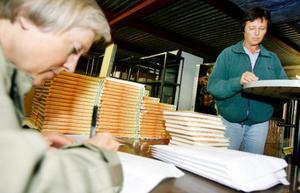 Arbetsmöte i boklagret. Ulla Wessling och Ylva Norrman träffades häromkvällen för att klistra in cd-omslagen på bokomslagens insida och skicka ut förbeställda böcker till köparna.  Foto: Henrik Flygare