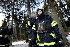 HJÄLP. Ola Johansson från Länsförsäkringar får hjälp att ta av sig den heta rökinpyrda utrustningen efter sin rökdykning.