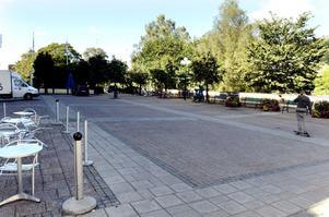Olof Palmes torg har inget intensivt folkliv en vanlig torsdag förmiddag. Träden och muren till höger skymmer dessutom sikten ner mot ån.