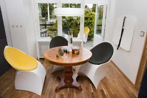 Gammalt och nytt. Ett modernt skafferi tar vara på kyla vid väggen. Stolarna kan vikas och hängas på väggen. Bordet är arvegods.