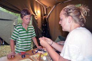 Luffarslöjd. Zebastian Almnor får instruktioner av Amanda Jeppsson om hur man gör en visp.