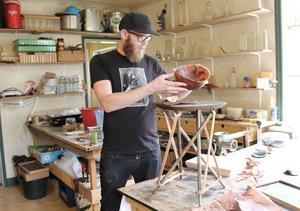 Erik Lith visar upp ett bord som företaget säljer. I handen håller han en skål som han har tillverkat av papper gjort på tall.