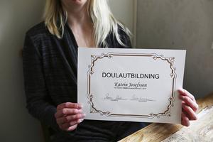 Här visar Katrin Josefsson sitt bevis för avklarad doulautbildning.