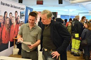 Kenneth Pettersson från Arbetsförmedlingen frågar Mathias Andersson från företaget Sykes Sweden i Sveg hur det går på mässan. Sykes behöver 36 personer till kundtjänsten för SAS räkning.
