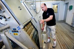 Claes Jakobsson visar ett filter i en av grovrensningsmaskinerna på Gövikens reningsverk. Efter att stora föremål filtrerats bort slår maskinen sönder resterna till en soppa och tvättar ur allt organiskt. De resterande fasta artiklarna pressas därefter samman, torkas, och hamnar i en container för senare förbränning.