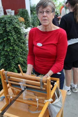 Kristina Johnsson väver i en barnvävstol och framhåller att det är hållbart med slöjd, då det går att välja material som håller länge.