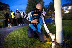 En av deltagarna i manifestationen Marcus Kalliomäki tänder det andra ljuset tillsammans med sonen och familjens lillhusse Noak.