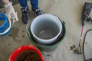 Ställ den mindre krukan i den större och fyll den med sten eller sand så den står stadigt.