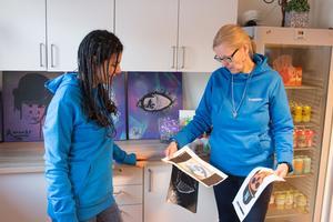 Sahar Shahidi och Carina Sörhammar tittar på målningar som ungdomarna på Unkan har gjort.