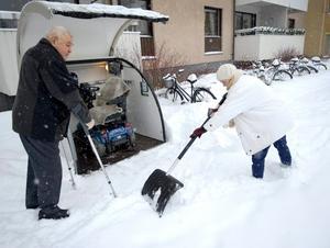 Precis utanför porten står Hans permobil i sitt lilla garage. Hustrun Mariana hjälper till att skotta så att han kan ta sig ut.