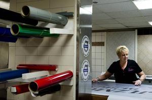 Monica Forsberg startade en egen designfirma. Sin egen företagslogga har hon inte hunnit med att sätta upp ännu. Här jobbar hon med att renskära de halvgenomskinliga fönsterloggorna.