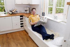 """Favorithörnan. På den platsbyggda soffan vid köksfönstret ligger Freddy ofta och läser tidningar eller pratar i telefon. """"Här har man en bra vy över hela utrymmet och här dricker lillkiller alltid morgonvällingen"""". Foto: Per Groth"""