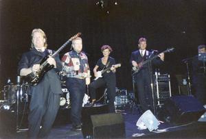 Tomas Jonsson i rutig skjorta 1995. Lotta Engberg i bakgrunden med gitarr backar upp.