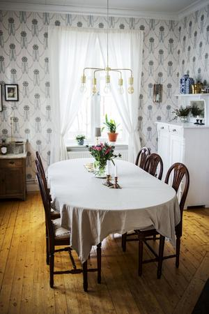 I matsalen möts gammal stil med moderna inslag. De flesta möblerna i huset är gamla medan mattor, lampor och konst ofta är samtida med en modern touch.