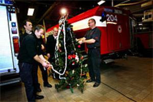 Julstämning i räddningstjänstens bilhall i Sandviken. Mats Carlsson, Thomas Andersson, Nisse Nordin och Lars Wallin ser till att lamporna i julgranen lyser. Att fira julafton på räddningsstationen har blivit en vana. Foto: Gun Wigh