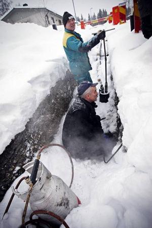 Fjärvärmerören som är på väg att installeras på Gudfastvägen i Valla har frusit. Därför måste Mats Mattsson från Klensmeden och Mikael Lindvall från Jämtkraft tina upp rören.