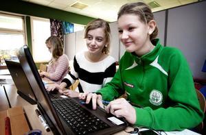 Sjätteklassarna Alva Österberg och Emma Ågren gillar sina nya datorer och ser bara kånkandet av dem, mellan hem och skola, som ett litet problem.