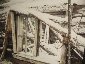Snön faller även på ruiner av en flottarkoja.