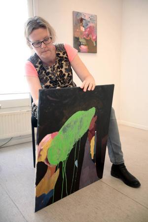 """Konstnären Elisabeth Athle signerar sitt verk """"Grönt möte"""" inför utställningen på Galleri Remi som öppnar i dag, lördag."""