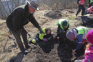 Ronnie Jensson från By Sockengille visar barnen att de grävt fram en av grundstenarna från torpet.