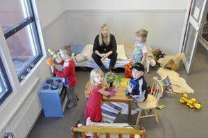 Förskollärare Monica Åkesson leker mamma-pappa-barn med Casper, Jasmine, Melvin och Linnéa.