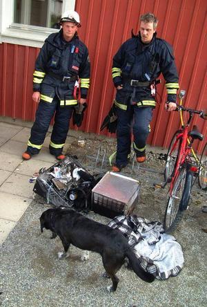 Brandmännen Bengt Olsson och Tomas Sjöström betraktar tillsammans med en av lägenhetens två hundar resterna av det som en gång var en spisfläkt.