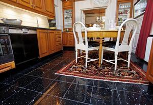 Köksgolvet har ett slående svartgnistrande golv. På det ligger en äkta matta - förstås.