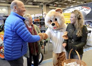 Hälsning. Björnen går armkrok med Liselott Lodén genom mässhavet. Ingemar Lindblom och Kerstin Fernkvist hälsar.