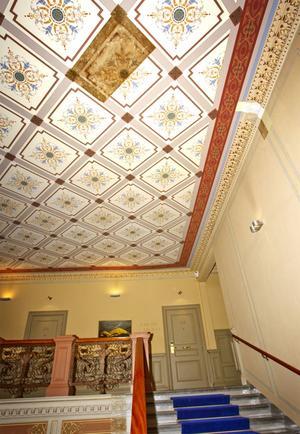 Här var tidigare överrollat med plastfärg, men med hjälp av Sundsvalls skickliga hantverkare har det vackra taket i trapphuset återställts. En dokumentruta har sparats som ett vittne på hur det såg ut i ursprungligt skick, så att det framgår vilka ledtrådar man haft.