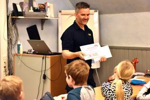 Stefan Glad ger klassen diplomet och femhundra kronor.