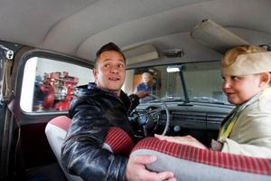 """Stickan testkör bilen efter att mekanikern Harry har lagat den. Här sitter han tillsammans med Bettan som jobbar på macken. Han ska köra bil från Östersund till Stockholm, för att sedan resa vidare till USA. """"Det är där det händer"""", säger Stickan."""
