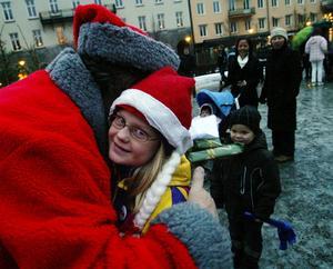 Selina Bjermkvist fick julklapp av Bergsjötomtens nissar och sedan en bamsekram av tomten själv.